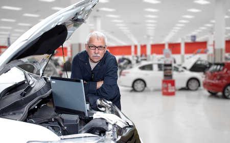 Sorridente garagista con chiave inglese in servizio di riparazione auto. Archivio Fotografico