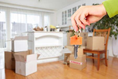 case moderne: Mano con la chiave di casa. Immobili e sfondo in movimento.