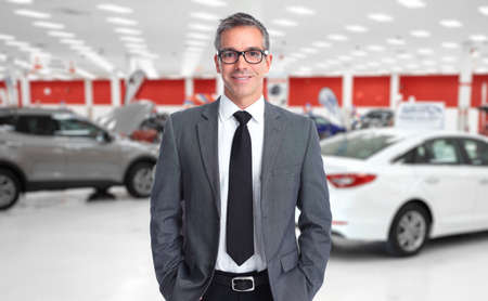car rent: Car dealer man. Auto dealership and rental concept background. Stock Photo