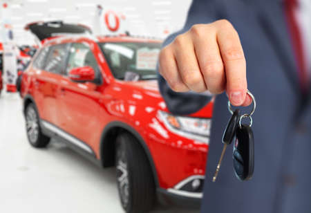 car rent: Car dealer with a key. Auto dealership and rental concept background. Stock Photo