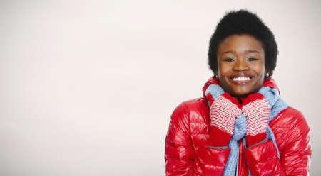 African-American Frau in Winterkleidung über Winter Hintergrund.