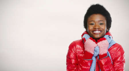 winter jacket: African -american woman in winter clothing over winter background.