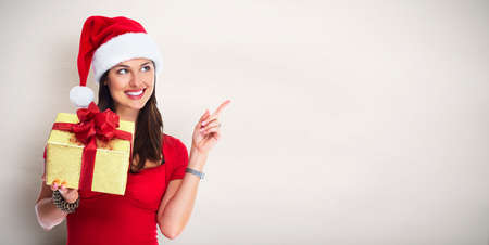 happy christmas: Happy Santa woman with Christmas gift over abstract background.