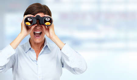 looking for job: Business woman with binoculars over blue background. Stock Photo