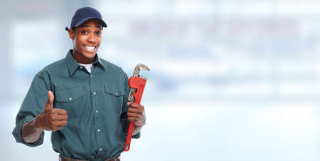 black guy: Plumber hands with a pipe wrench over blue banner background. Stock Photo