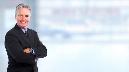 profesionistas: Empresario maduro sonriente sobre fondo azul Foto de archivo