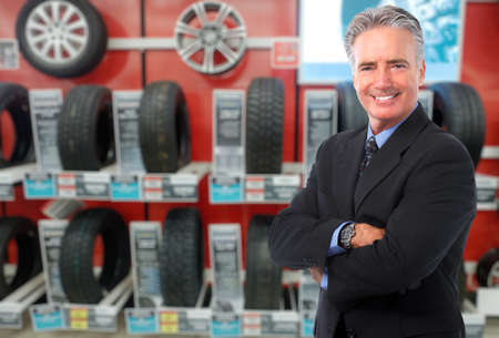 selling service smile: Car dealer man over tire tire background. Auto maintenance.