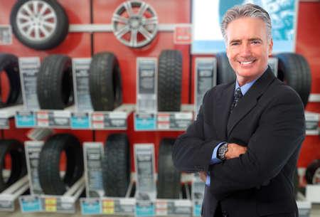 llantas: Concesionario de coches el hombre sobre fondo neumático. Mantenimiento automático.