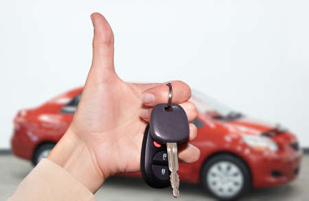 new car: Driver hand with a car key over new vehicle background.