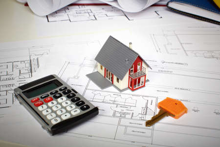 cost: Little house and calculator on the table. Construction and architecture.