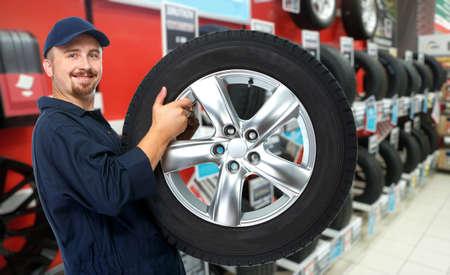 Usmívající se automechanik s pneumatikou přes garáž pozadí.