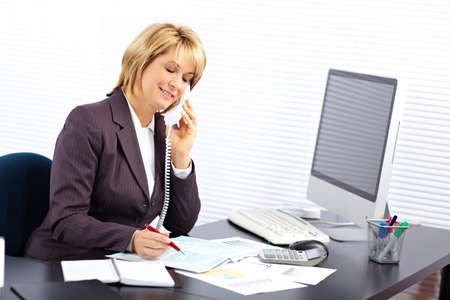 business woman working: Beautiful mature business woman working in modern office. Stock Photo