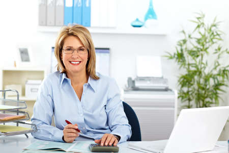 business woman: Beautiful mature business woman working in modern office. Stock Photo