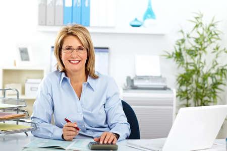 mujer trabajadora: Hermosa mujer de negocios maduros de trabajo en la oficina moderna.