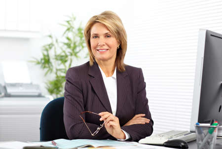 woman in office: Mature business woman working with computer in the office.