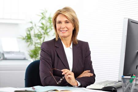 Starší obchodní žena pracující s počítačem v kanceláři.