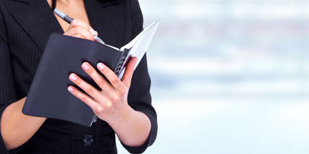 diaries: Hands of young business Woman writing in a diary book. Stock Photo