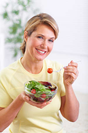 eating salad: Elderly woman eating salad. Diet and nutrition concept background.