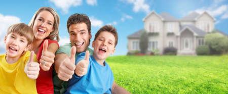 cielo azul: Familia feliz con los niños cerca de casa nueva. Construcción y bienes raíces concepto.