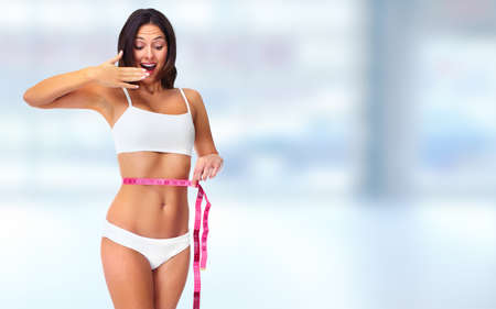 measure: Young woman with measuring tape. Weight loss and dieting.