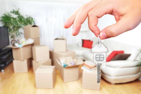 Hand mit Haus-Taste. Immobilien und beweglichen Hintergrund.