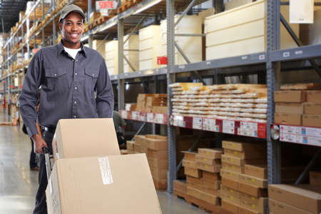 delivery service: Delivery postman with a box over stock background. Stock Photo