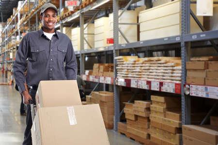 postino consegna con una scatola su sfondo magazzino. Archivio Fotografico