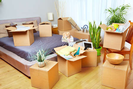 house moving: Moving boxes in new house. Real estate concept.