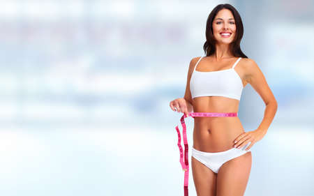 losing weight: Young woman with measuring tape. Weight loss and dieting.