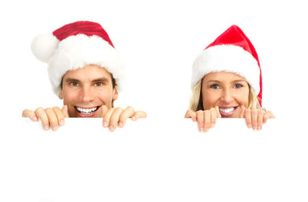 plackard: Young happy couple in Christmas hats. Isolated over white background