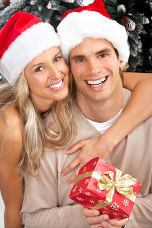 christmas gift: Young happy couple near  a Christmas tree. Isolated over white background  Stock Photo