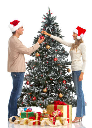 winter woman: Young happy couple near  a Christmas tree. Isolated over white background