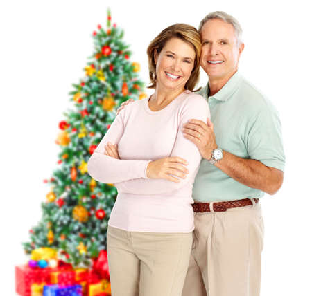 couple winter: Elderly  happy couple near a Christmas tree. Isolated over white background