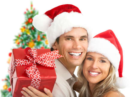 christmas gift: Young happy couple near  a Christmas tree. Isolated over white background