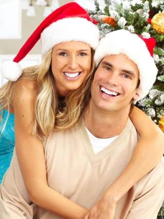 winter woman: Young happy couple near  a Christmas tree at home
