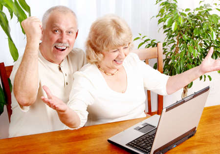 senior ordinateur: Couple senior travaillant avec un ordinateur portable � la maison  Banque d'images