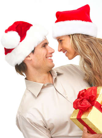 christmas gift: Young happy couple in Christmas hats. Isolated over white background