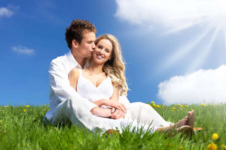 loving couples: Young love couple smiling under blue sky  Stock Photo