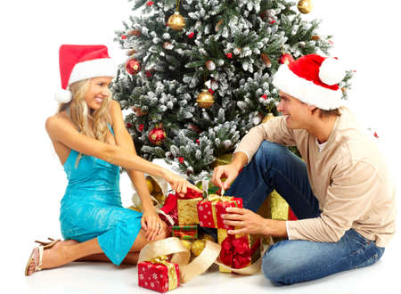 christmas gift: Young happy couple near  a Christmas tree. Over white background