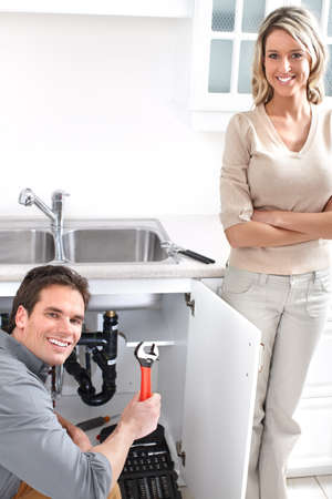sink drain: Young plumber fixing a sink   Stock Photo