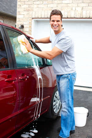 car wash: Smiling happy man washing the red car  Stock Photo