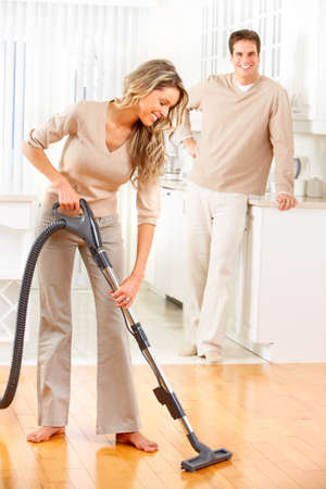 vacuum cleaning: Housework, vacuum cleaner, young couple, home, kitchen. Housework