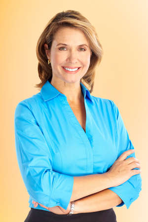 mujeres maduras: Sonriente mujer de negocios. Sobre fondo marr�n Foto de archivo