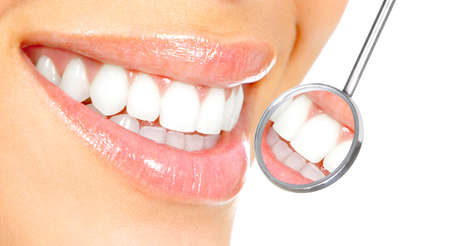 dentists clinic: Healthy woman teeth and a dentist mouth mirror  Stock Photo