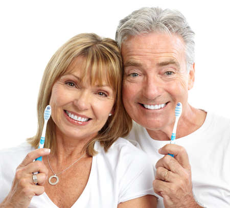 brushing: Happy seniors couple with toothbrushes. Healthy teeth. Isolated over white background  Stock Photo