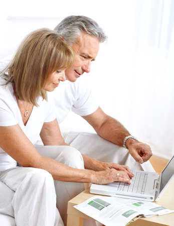 technology: Seniors couple  working with laptop at home