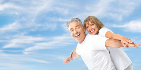 retire: Happy smiling elderly seniors couple under blue sky