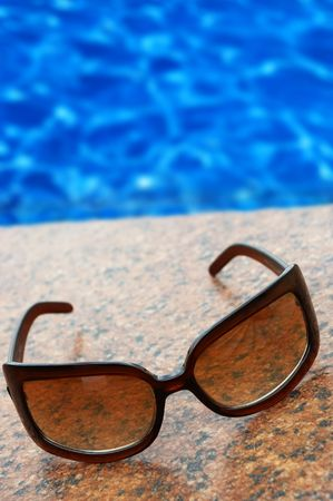 sun glasses and blue pool(focus point on the right lower part of sun glasses)