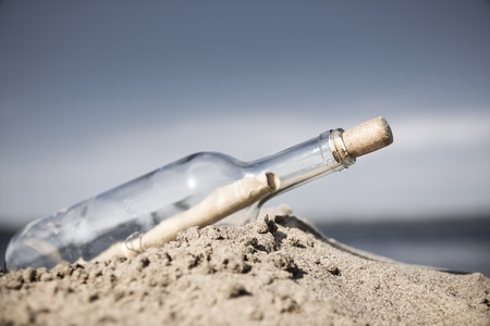 glass bottle with note washed up on the beach photo