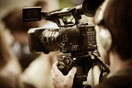 hombre disparando: cámara de vídeo profesional en el enfoque trípode, selectivo en la parte más cercana Foto de archivo
